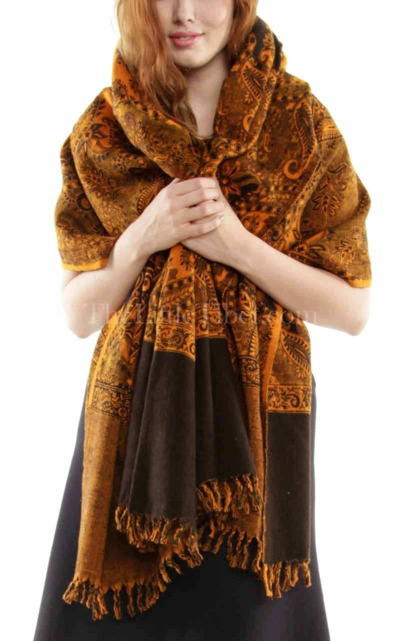 woman holding orange gold paisley design reversible himalayan tibet shawl