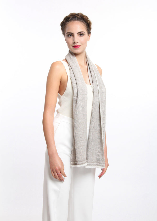 Close up creamy beige with brown pattern detail 100% pure cashmere scarf draped around shoulders