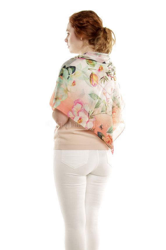 Close up 100% pure silk with floral peach green pink detail draped around shoulders