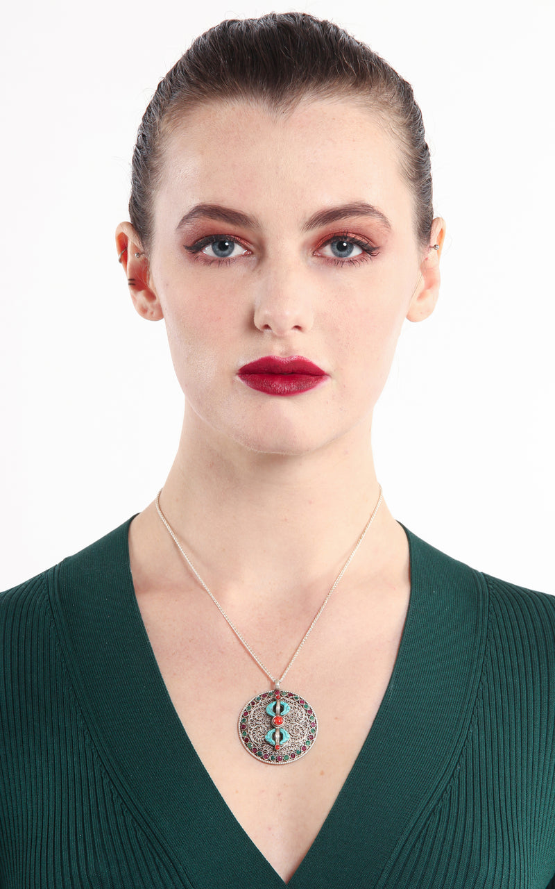 model wearing Silver Dorjee Pendant turquoise coral ruby emerald embellishment