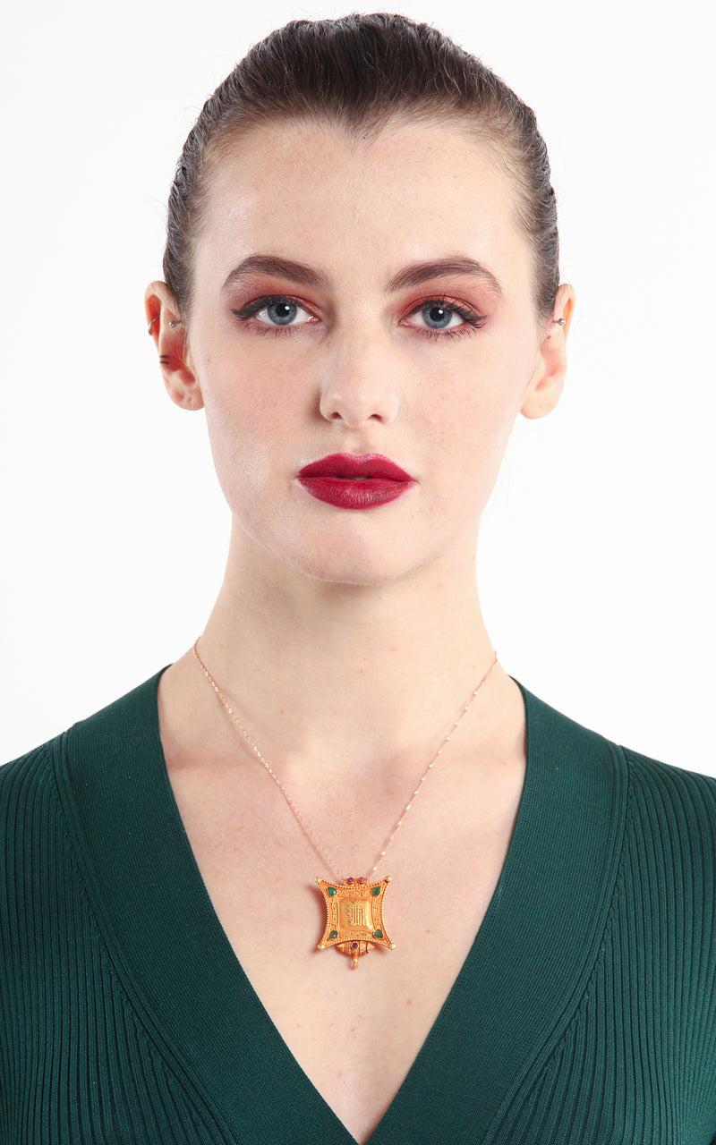 model wearing Gold Kalachakra Wheel of Time Locket Pendant ruby emerald accents