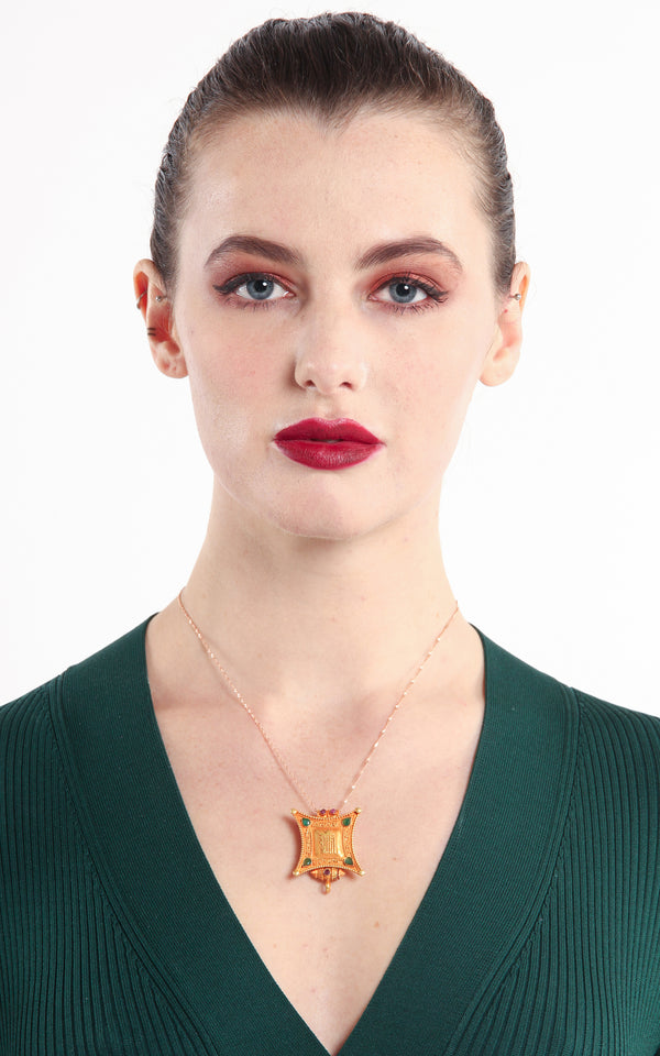 model wearing Gold Plated Om Locket Pendant with ruby emerald stones