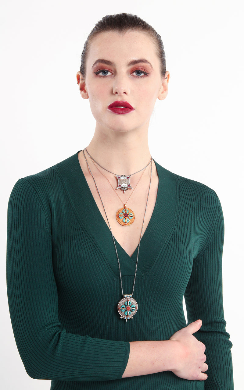 model wearing circular Gold Om Locket Pendant turquoise coral detail