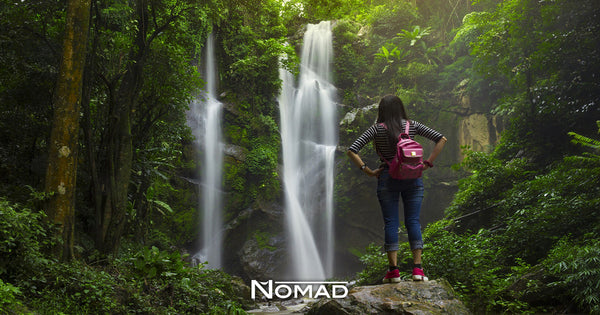 Get Up and Leave - Why You Should Travel Today - Featured Image - Backpacker In Woods Viewing Waterfall