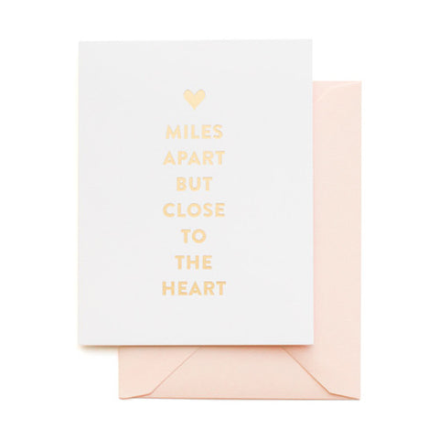 White card printed gold foil printed with Miles Apart But Close to the Heart