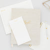 Stacked note pads and agenda in white and gold