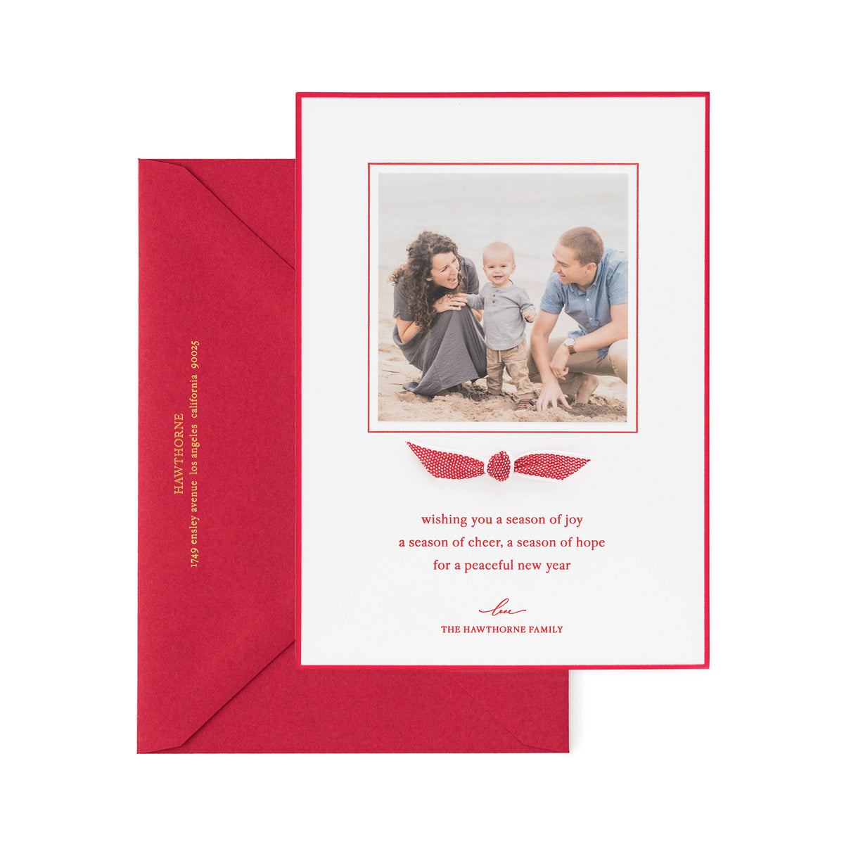Red holiday photo card with a red and white ribbon showing detail of the gold foil on the envelope.