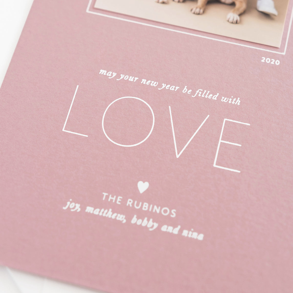 Closeup of dusty rose holiday card showing white foil text