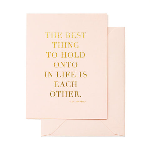 "Pale pink card printed in gold foil with ""The Best Thing to Hold Onto in life is each other"