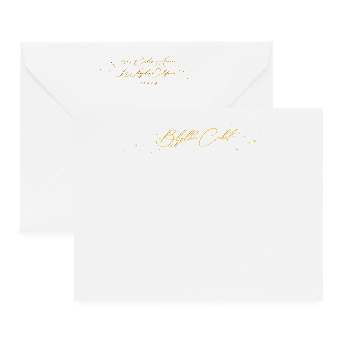 White stationery set with gold foil script name and gold return address detail