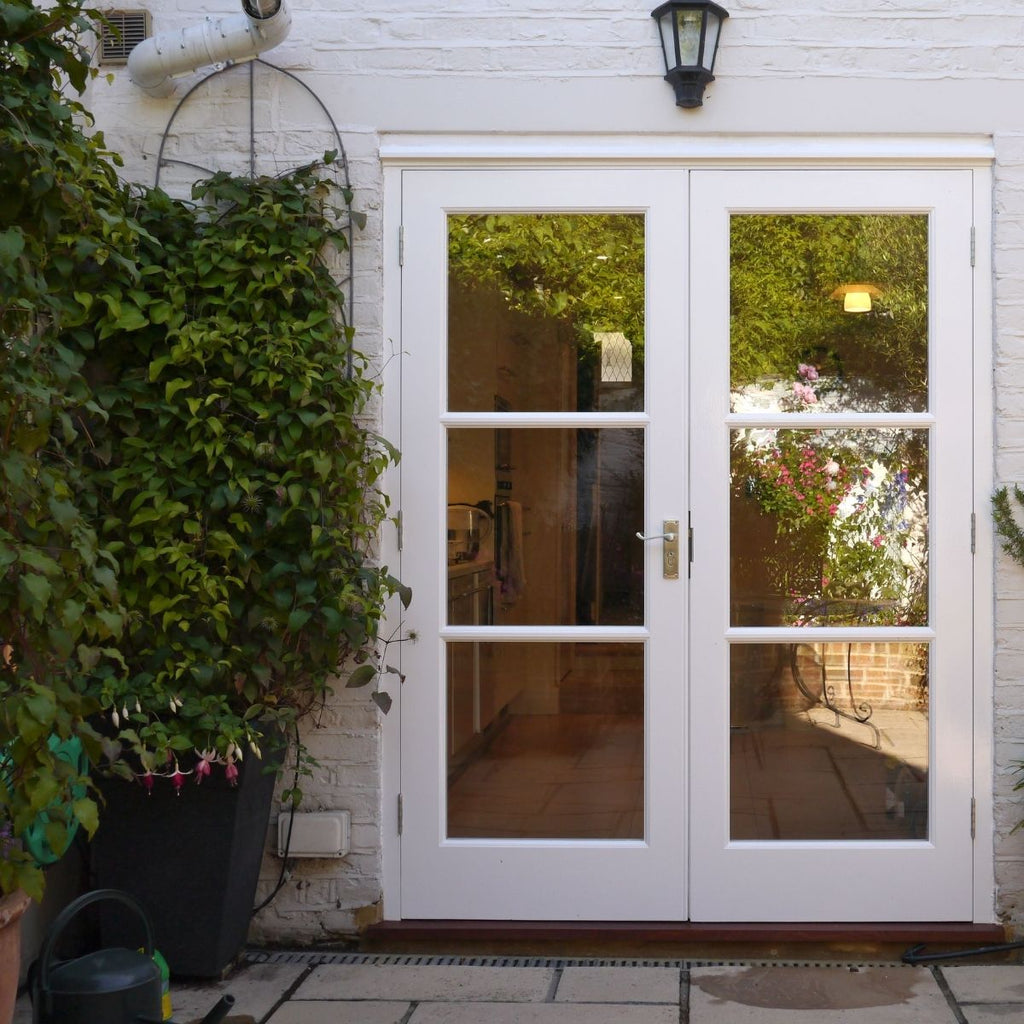 white exterior home with double french doors
