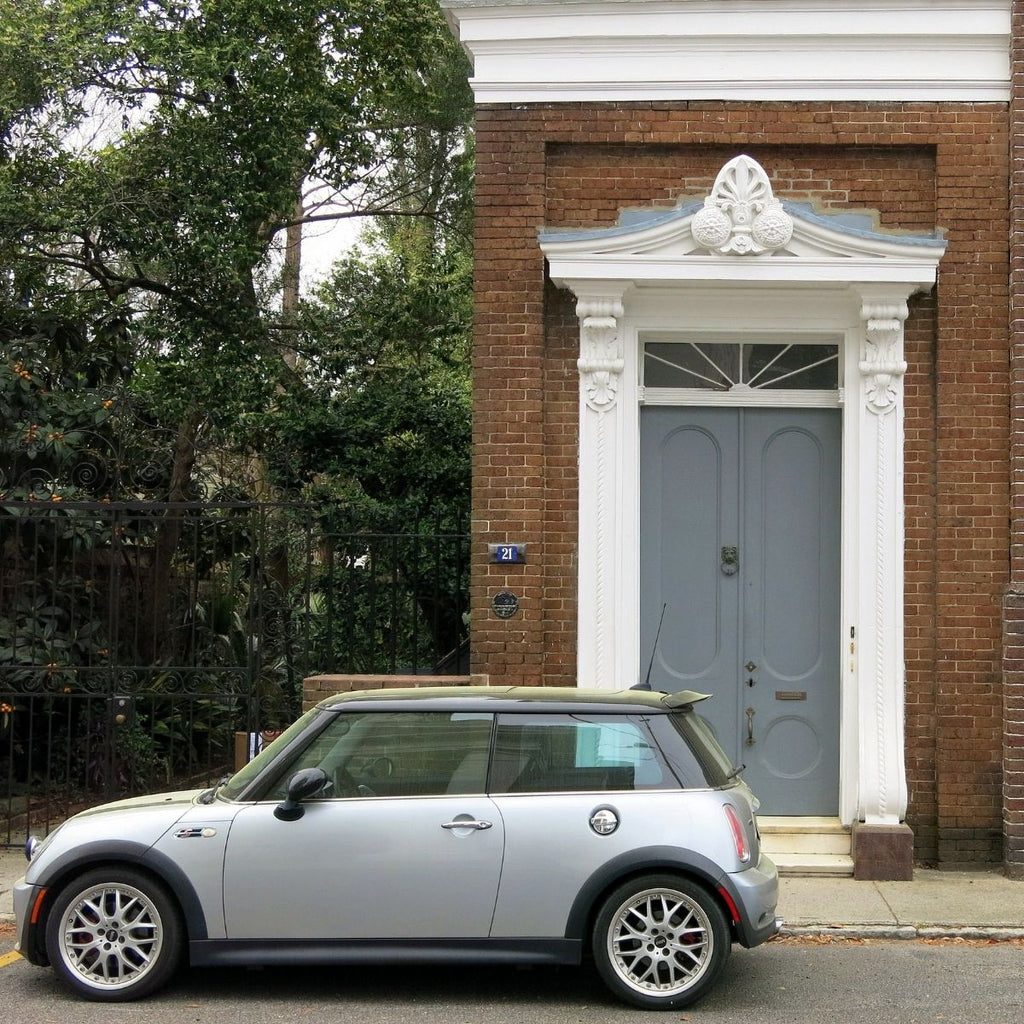 brick house with grey/blue door with silver car in front