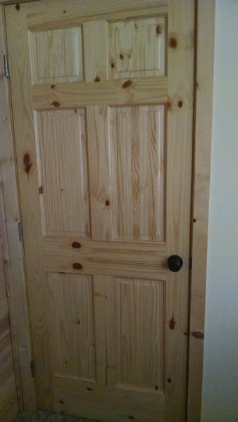 knotty pine door in a cabin purchased online from dtd