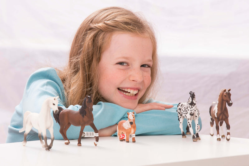 Schleich horse toys being played with by young girl.