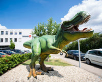 Schleich headquarters with a green life-sized T-Rex in front of the building.