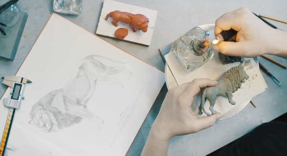 Artist drawing of a lion during the Schleich creation process. Tools are shown to ensure scale accuracy.