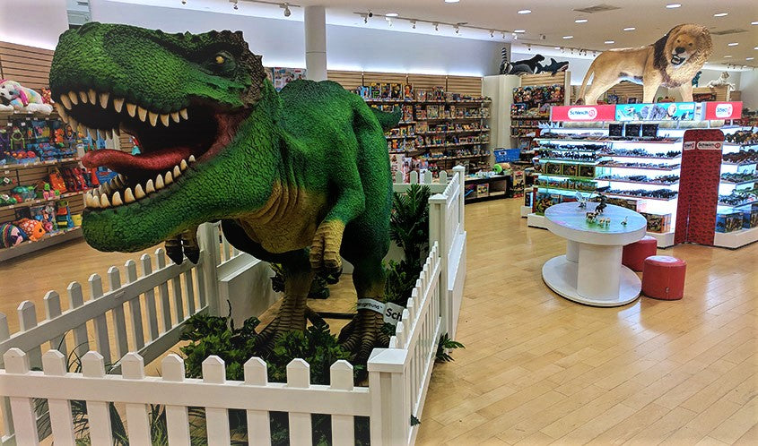 14 foot green T-Rex in a fenced in area and a life-sized lion that sits on top of a gondola of Schleich products, which is located at Maziply Toys, the US flagship store for Schleich.