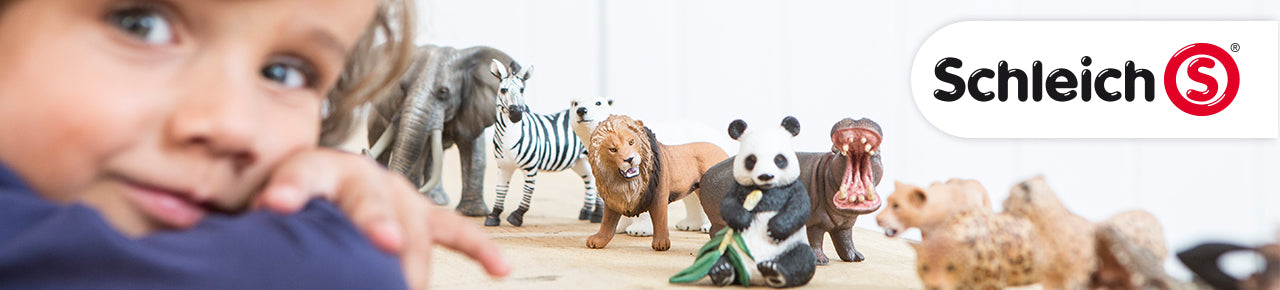 Schleich Brands are represented with this image of a child leaning on a table that has multiple Schleich animals, including an elephant, zebra, lion, panda, hippo, and Schleich logo.