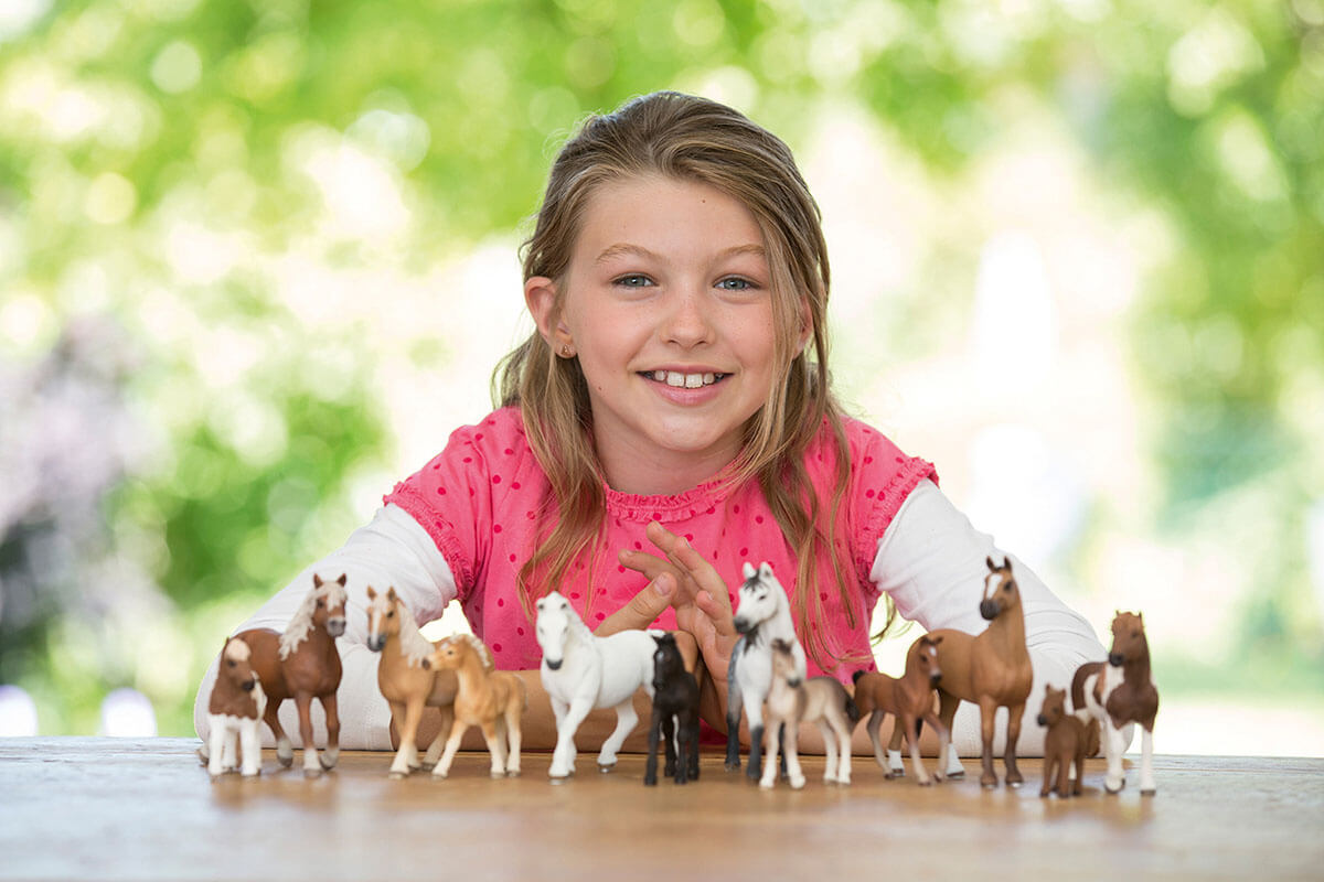 Schleich horse toys are placed in front of a happy girl. There are stallions, mares, ponies, and foals.