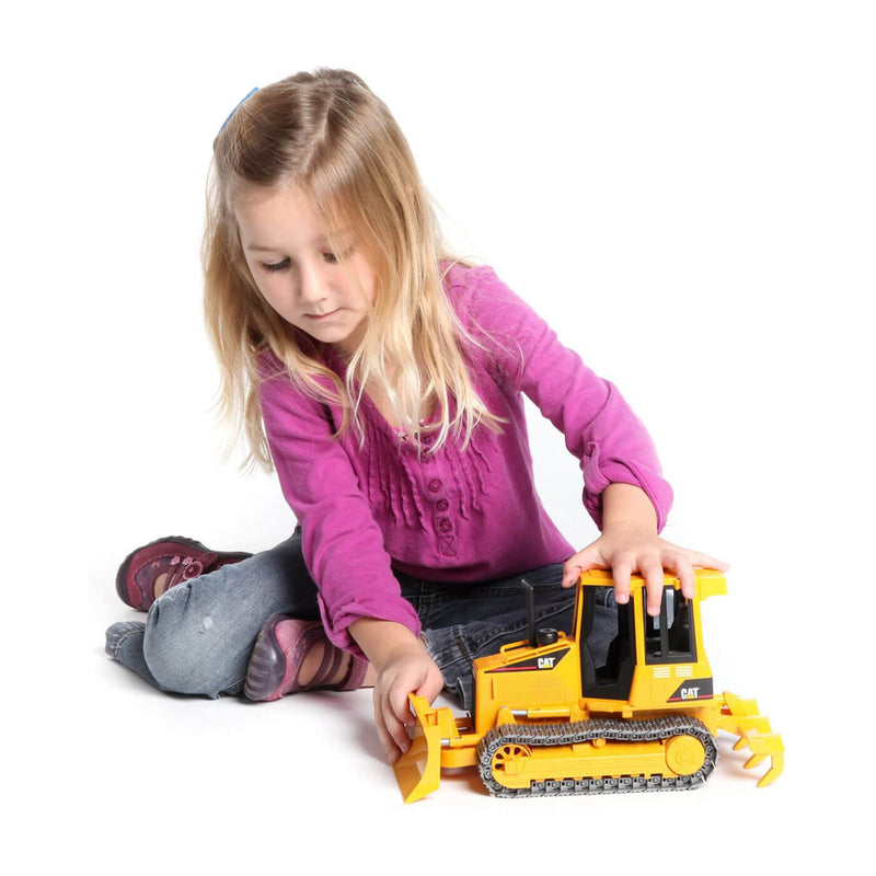 Kid playing with the tractor vehicle toy.