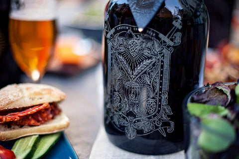 Our hops and wheat crest, customized with a name and engraved on this 64oz growler. Containg delicious craft beer and decorating the table with art.