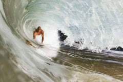 Rusty using body surfing hand board / hand plane to bodysurf in the barrel in Hawaiian shorey