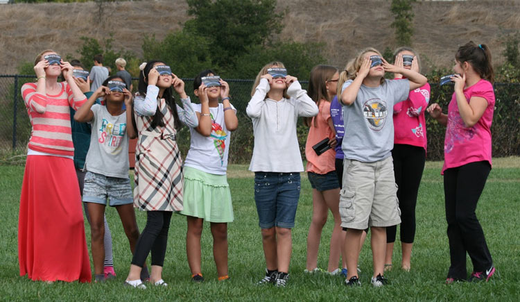 Children Looking at solar eclipse through Rainbow symphony eclipse shades.