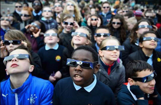 Children Watching solar eclipse safely through rainbow symphony eclipse-glasses