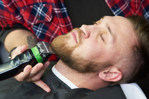man relaxing at barbershop beard trim