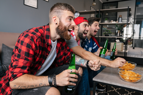 group of guys watching a football game on tv
