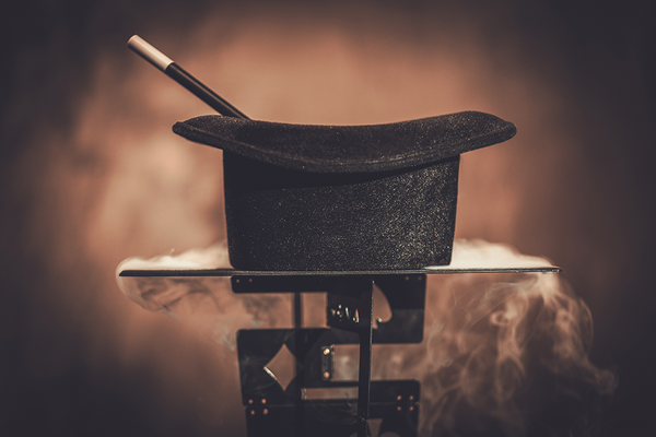 A black top hat sits upsidown on a smoking table, held up by metal playing cards.  A magic wand is inside the hat