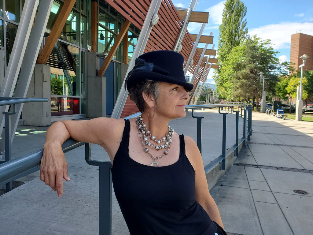 Woman wearing a Canadian made necklace and black hat