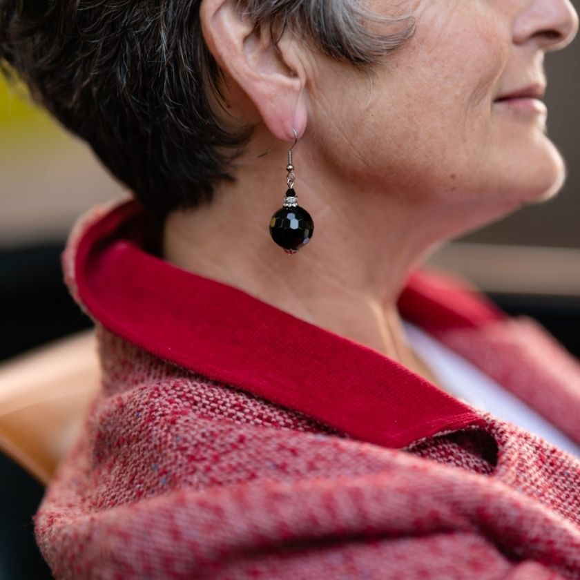 Black onyx earring hanging on a woman's ear who is in her fifties
