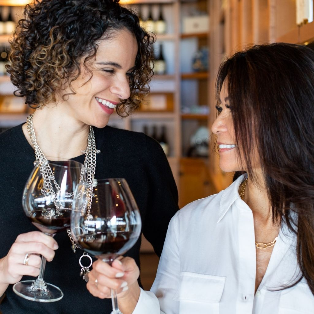 Two smiling women wearing Carolily Finery statement necklaces cheers their wine glasses