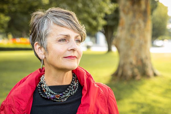 a middle aged woman with short hair wearing a black onyx necklace and silver hoop earrings