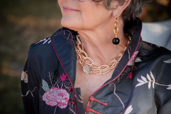a closeup of a woman wearing a gold necklace and gold onyx earrings
