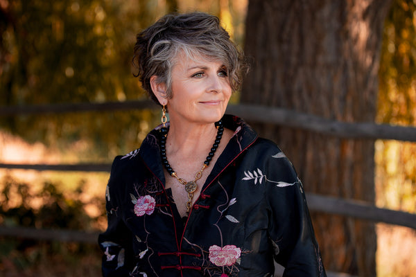 A woman in a jacket wearing a gold and black onyx necklace and pair of earrings