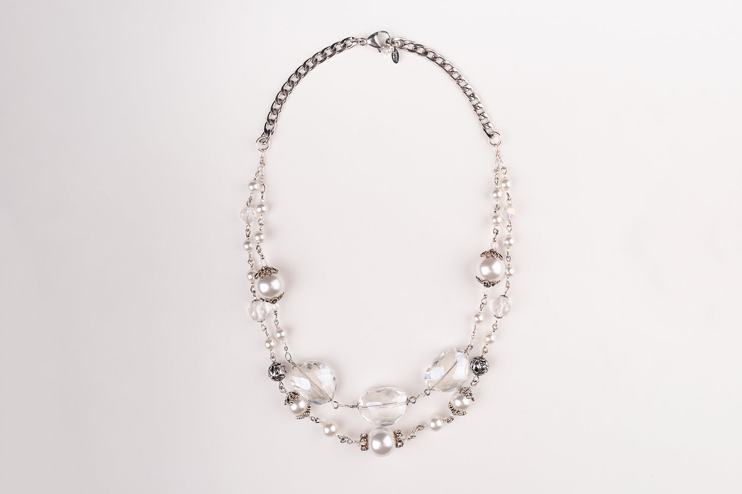 A Carolily Finery statement necklace made from sterling silver, large faceted crystal and Swarovski crystal pearl hanging in front of a white backdrop