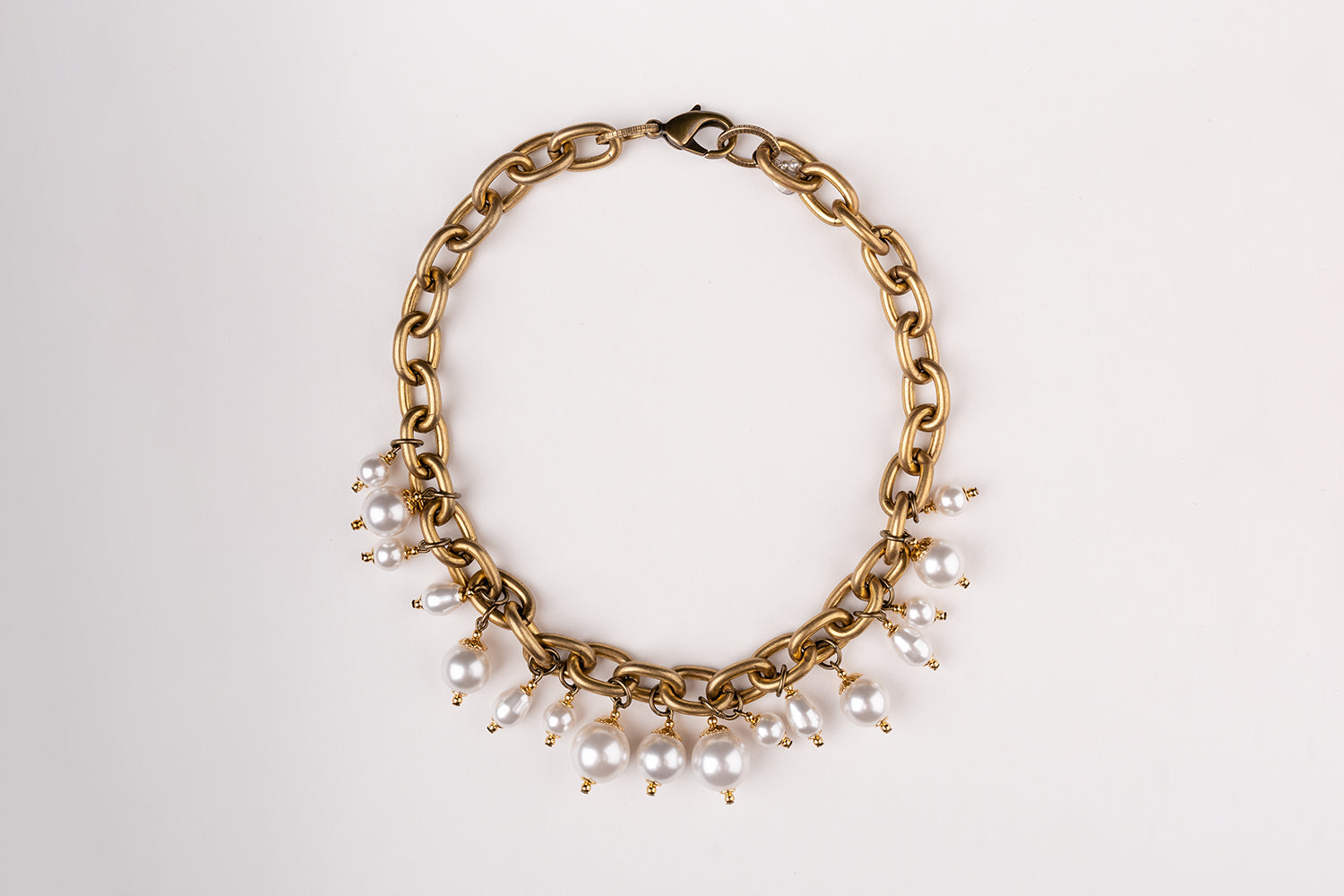 A Carolily Finery statement necklace made from antique gold chain and Swarovski crystal pearls
