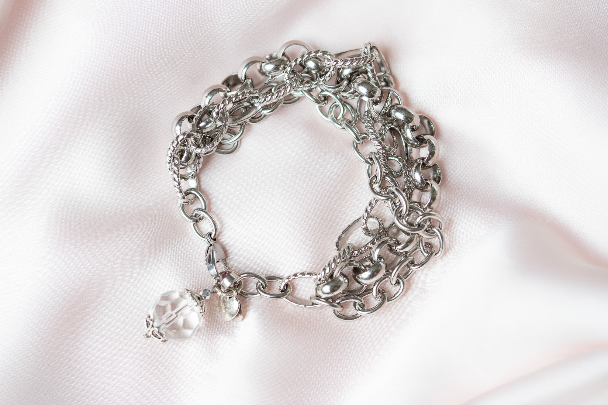a Carolily Finery bracelet made from stainless steel chain, rose quartz and crystal