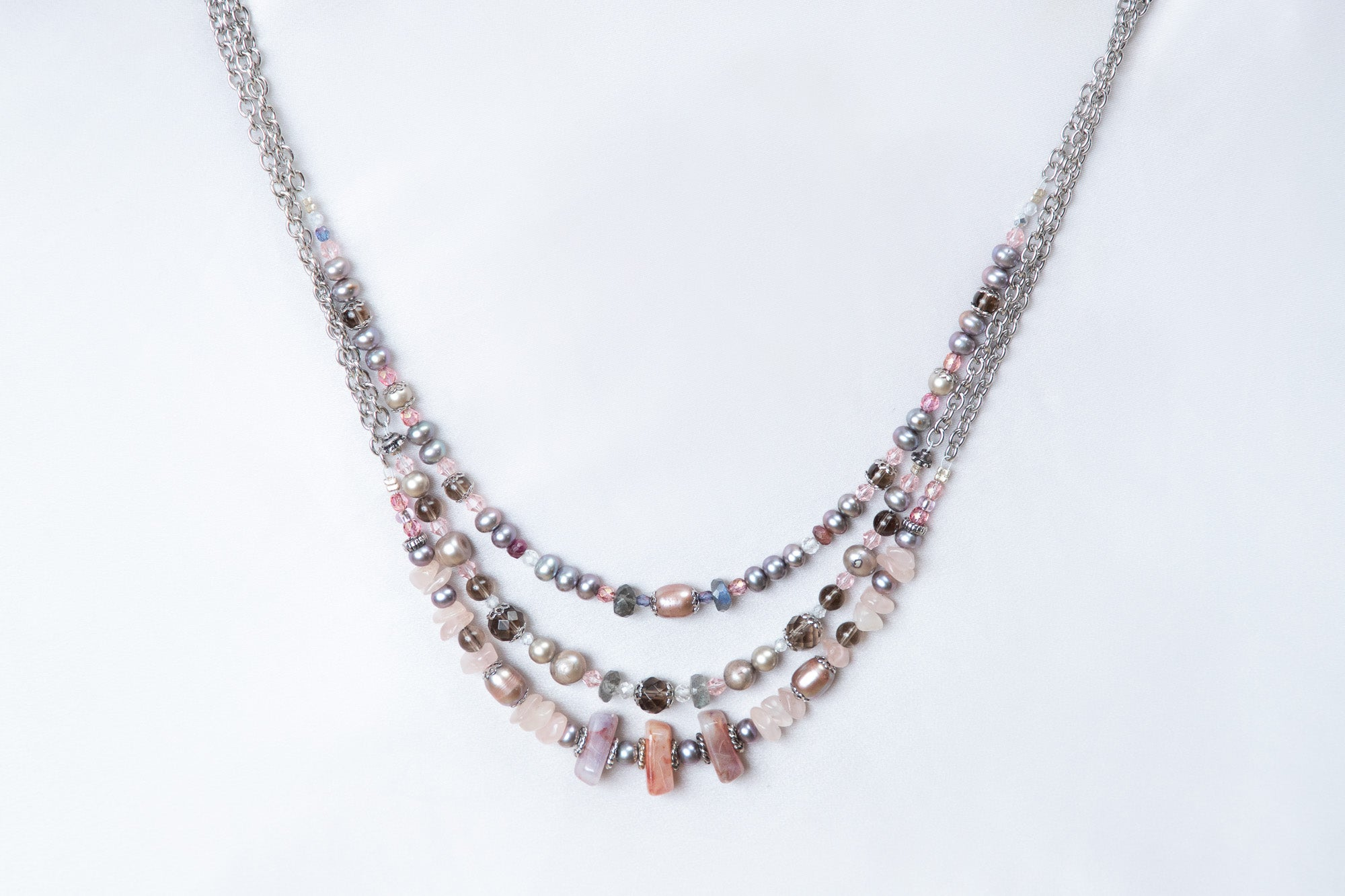 A Carolily Finery statement necklace made of gemstones, silver and Swarovski crystal pearls hanging in front of a white back drop