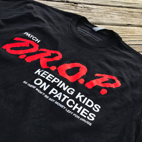 "Dangerous Goods™ Patch Drop ""Keeping Kids On Patches"" T-Shirt - 2 Color Options"