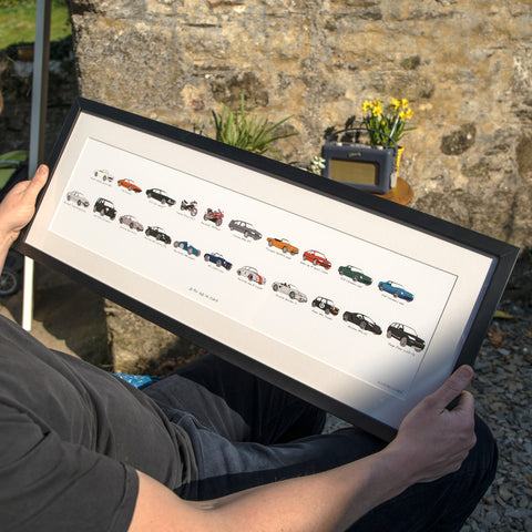 man holding his car history artwork in a frame. my life in cars. Carvolution® Your life in cars, bespoke car art, car history gift, carvolution logo, car logo, my life in cars, car gift for men, personalised car artwork, framed car artwork, car drawings, classic car drawings, framed artwork, artwork delivery, artwork lifestyle shot, life style photography, professionally framed artwork, fine art guild framers, above and beyond personalised gift, bespoke car print, framed car artwork, dry mounted prints.