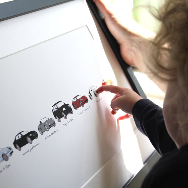 Pointing at artwork. Artwork includes persons car history. Maserati. Range Rover sport. Porsche Boxster S. Your life in cars framed artwork. child pointing at dads bespoke artwork.