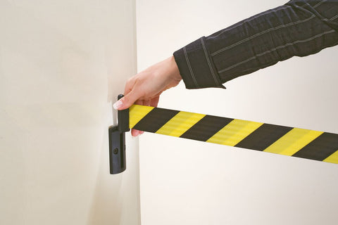 wall mounted belt barrier yellow and black hazard stripes