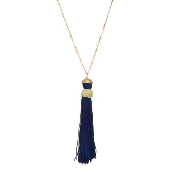 Gold necklace with royal blue tassel with braided cream cord.