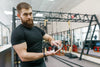 best multivitamin for men: a man inside a gym while pouring vitamins on his hands