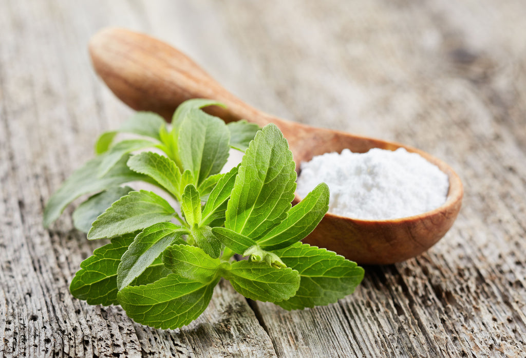 Stevia plant beside white powder in wooden spoon on wooden surface