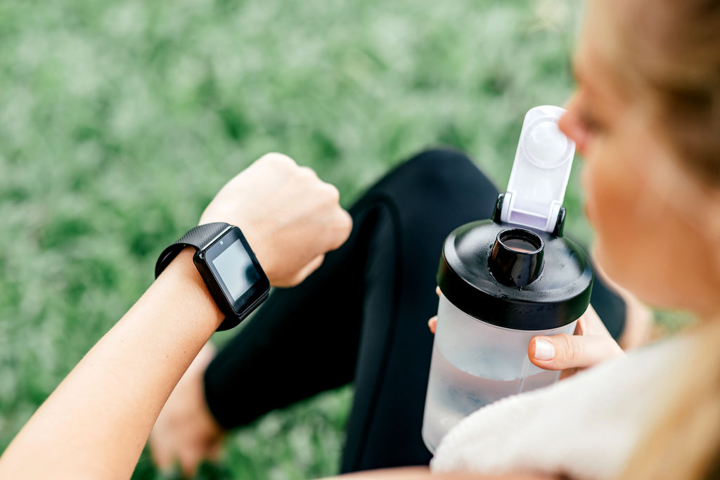 Woman looking at her watch and drinking preworkout