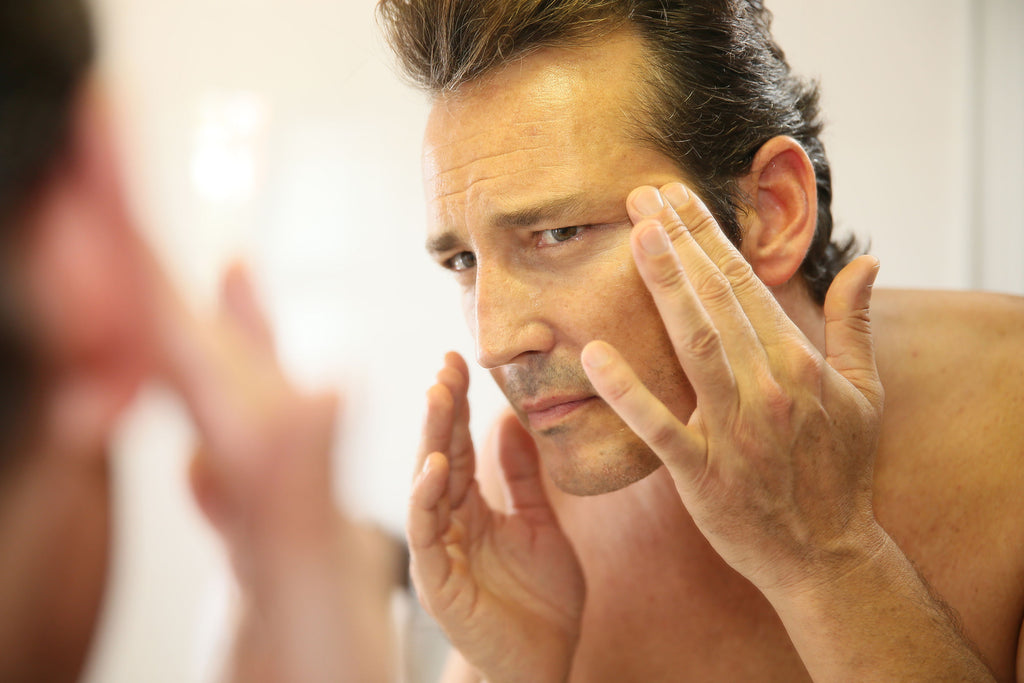 Middle-aged man looking into the mirror noticing wrinkles in his skin